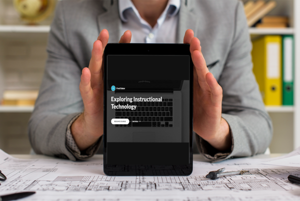 Person holding a tablet displaying the Exploring Instructional Technology Course on it